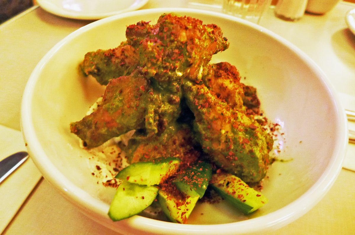 Green chicken wings heaped up in a bowl with cucumbers.