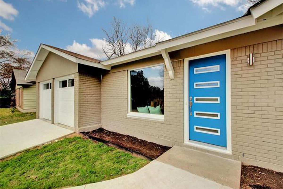 Gray midcentury with bright blue door, shot fairly close up from angle, picture window