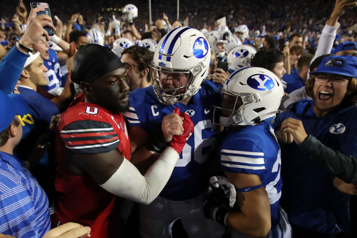 Utah linebacker Devin Lloyd (0) and BYU center James Empey (66) greet each other after the Cougars' 26-17 victory over Utah.