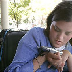 Jamie Moore, who has been quadriplegic since she was 5, works to hang up her cell phone. She grew up in Delta and is now a student at BYU.
