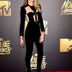 Cara Delevingne wears a black Balmain jumpsuit and a 90-degree angle braid.