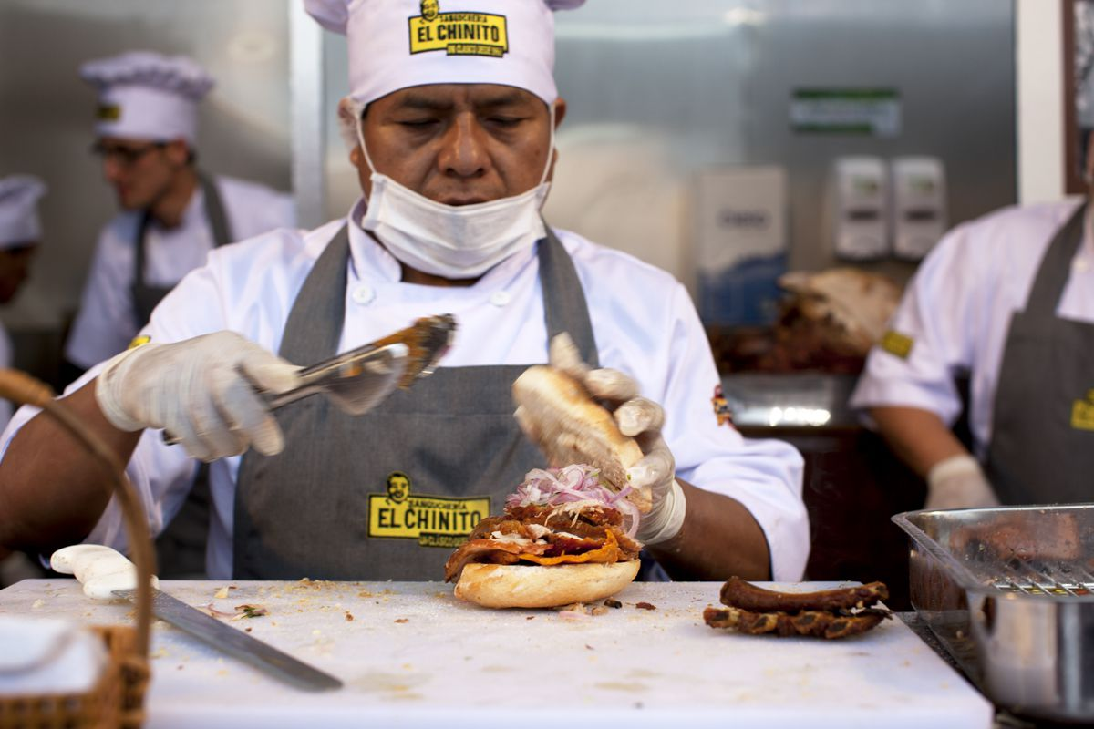 A server in a branded apron and chef's toque lifts the top bun of a sandwich while using tongs to add ingredients.