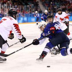 Jocelyne Lamoureux #17 of the United States shoots against Lauriane Rougeau #5 of Canada.
