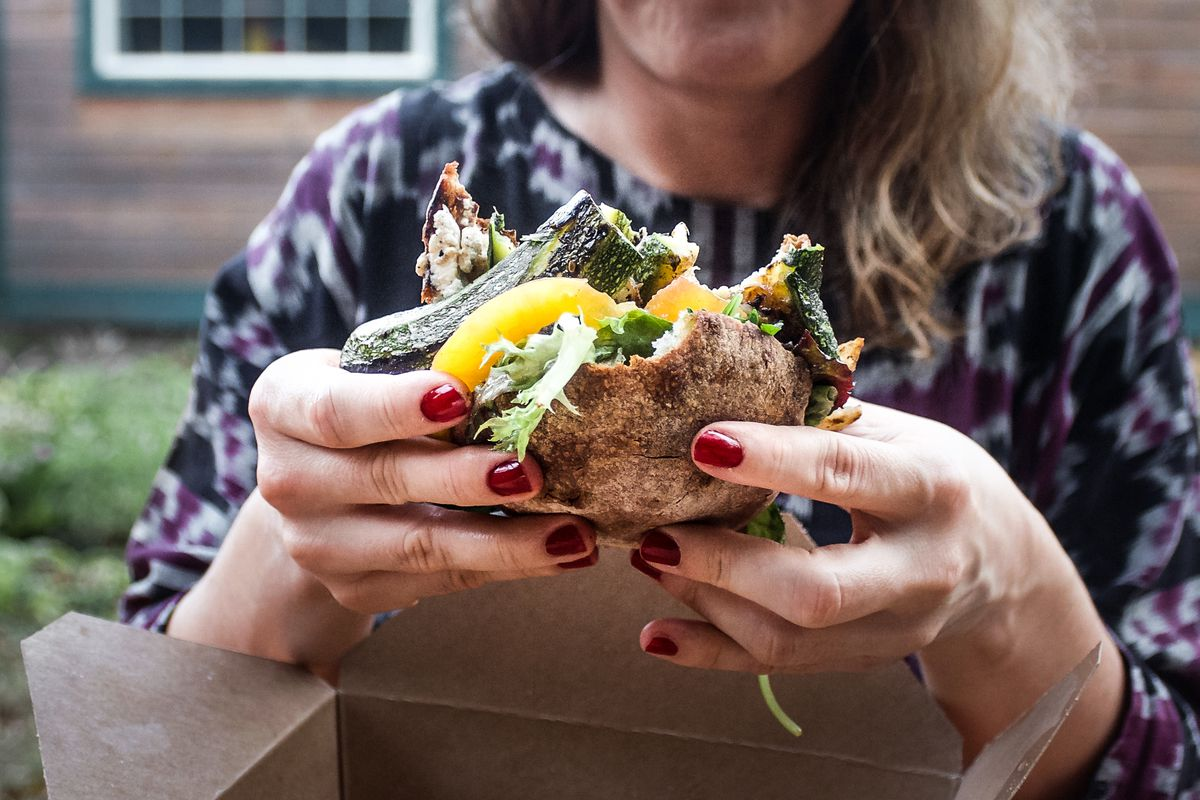 A woman with red-painted fingernails holds a sandwich with pieces of zucchini and bell pepper at Sorbu Paninoteca