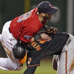 Boston Red Sox second baseman Dustin Pedroia, left, collides with Baltimore Orioles' Mark Reynolds, who is out at second while unsuccessfully trying to break up a double play, during the sixth inning of a baseball game at Fenway Park in Boston, Friday, Sept. 21, 2012.