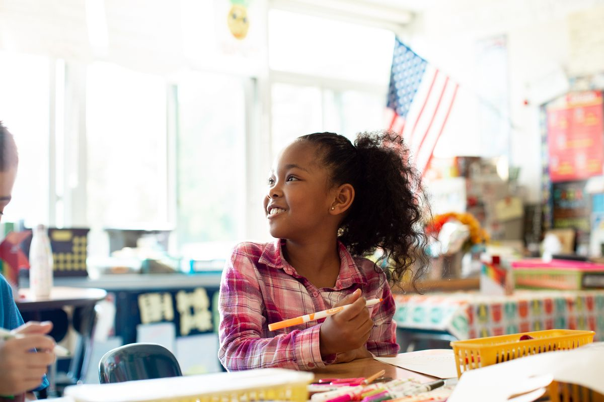 A student is holding a marker, seated at a desk in a classroom, and smiling.