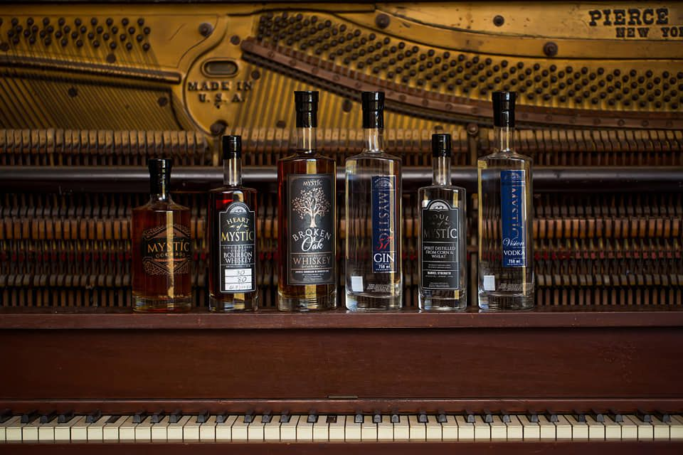 Bottles of Mystic Farm and Distillery booze on an old piano