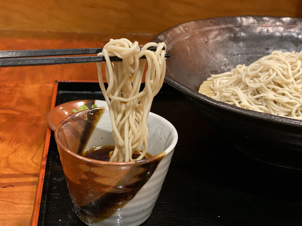A patron dips buckwheat noodles into a ceramic cup, filled with tsuyu