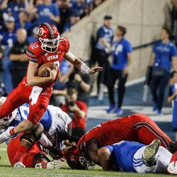 Utah Utes quarterback Charlie Brewer dodges a tackle during the first half of an NCAA college football game against BYUat LaVell Edwards Stadium in Provo on Saturday, Sept. 11, 2021.