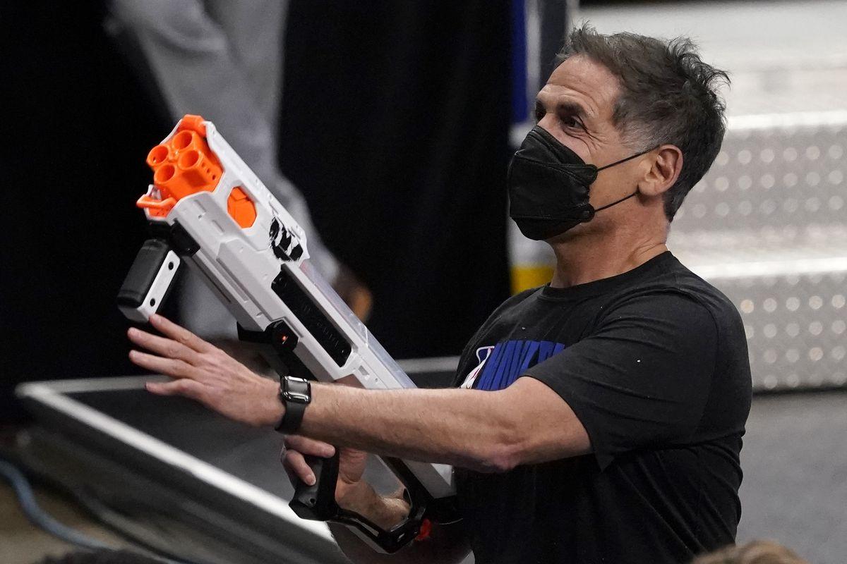 Dallas Mavericks owner Mark Cuban shoots toy gun ammo at an NBA basketball game.