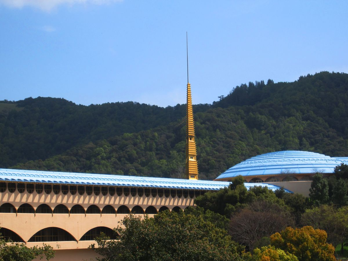 Marin County Civic Center by Frank Lloyd Wright. The roof is blue and the facade is tan. There is a gold spire. In the background are hills.