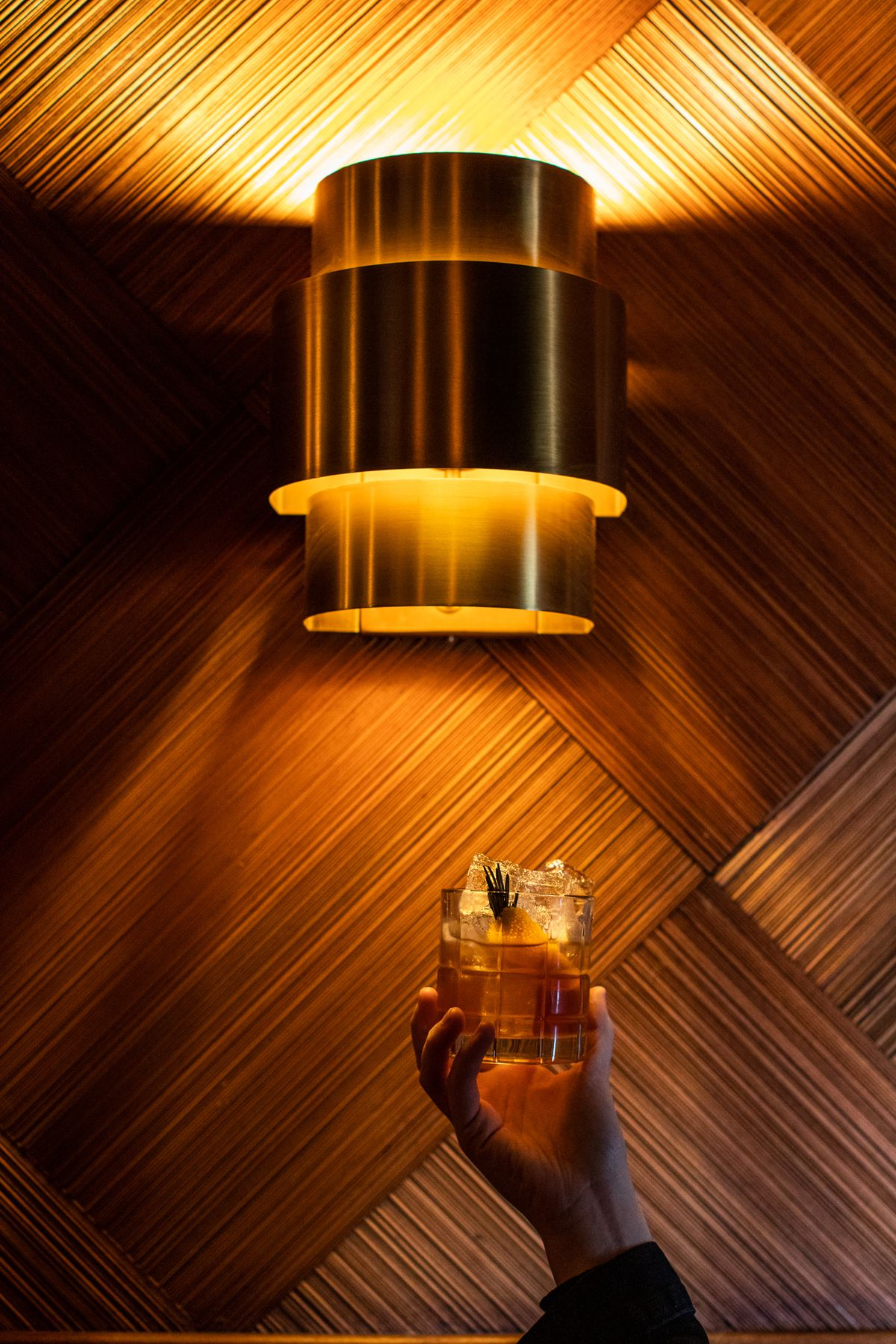 A hand holds up a tumbler of a brown cocktail with pieces of ice below an art deco-style sconce. The cocktail is garnished with orange peel and rosemary.