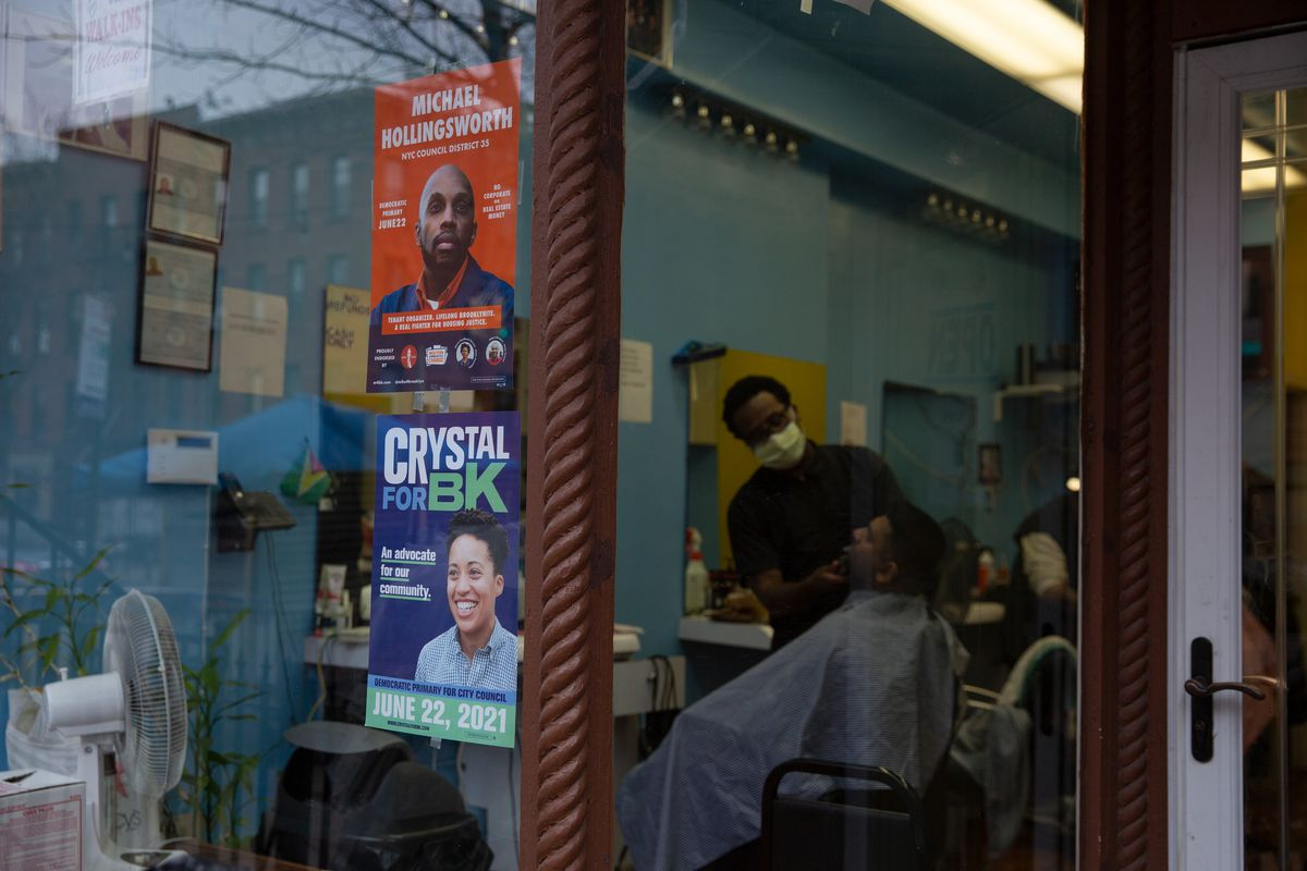 Campaign posters for Michael Hollingsworth and Crystal Hudson compete at a barbershop in Prospect Heights, Brooklyn, March 16, 2021.