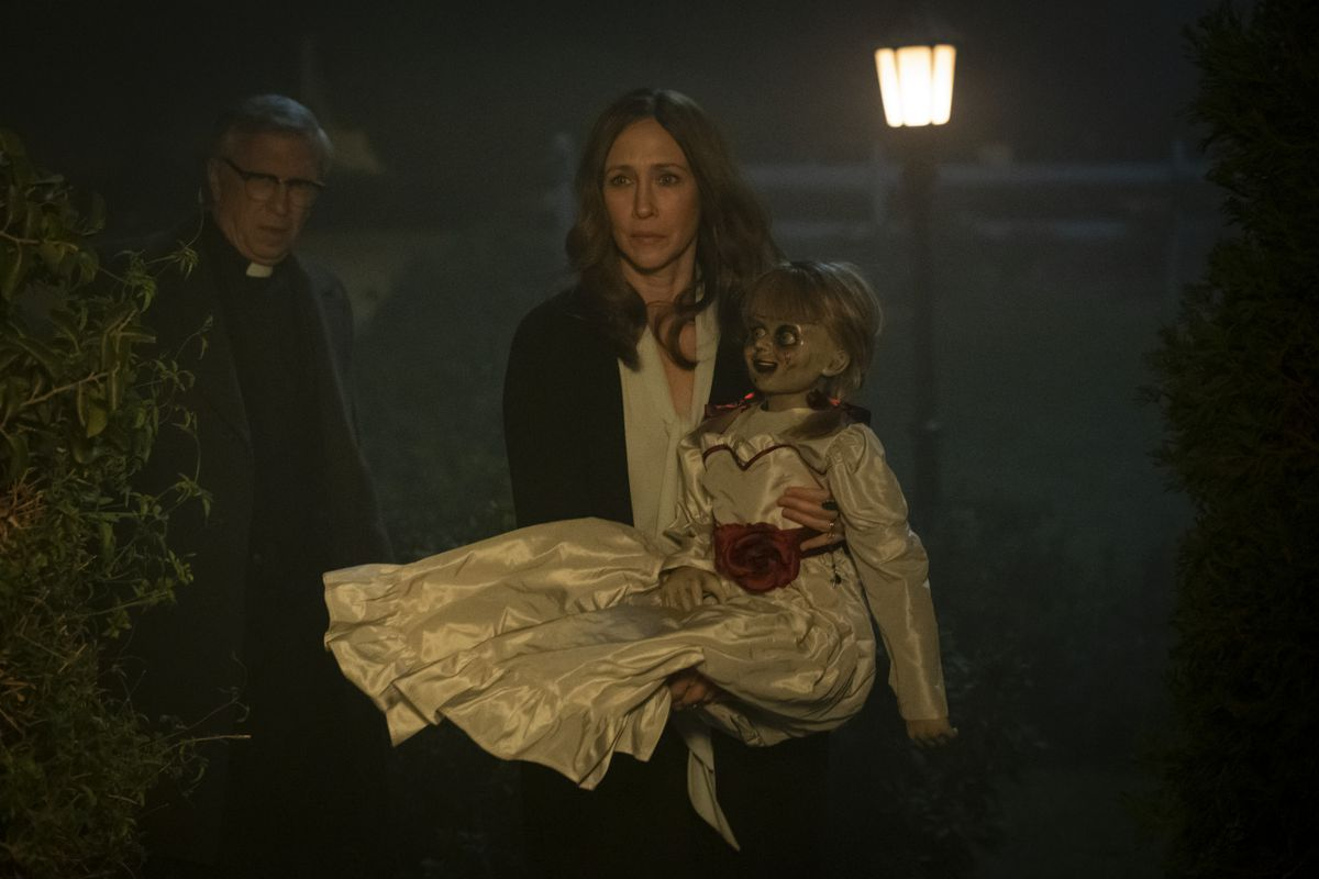 """STEVE COULTER as Father Gordon, VERA FARMIGA as Lorraine Warren and the Annabelle doll in New Line Cinema's horror film """"ANNABELLE COMES HOME,"""" a Warner Bros. Pictures release."""