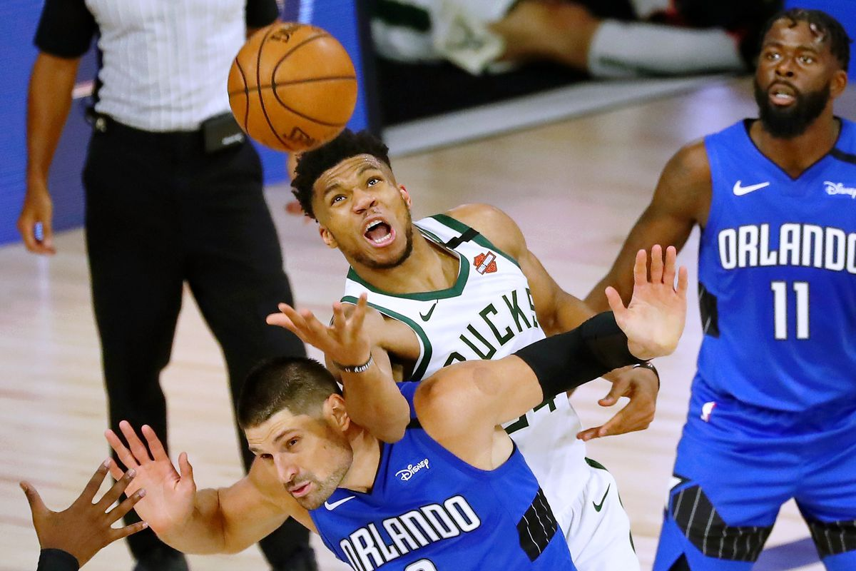 Giannis Antetokounmpo of the Milwaukee Bucks fouls Nikola Vucevic of the Orlando Magic while reaching for a loose ball in the second half during Game One in the first round of the NBA playoffs at The Field House at ESPN Wide World Of Sports Complex on August 18, 2020 in Lake Buena Vista, Florida.