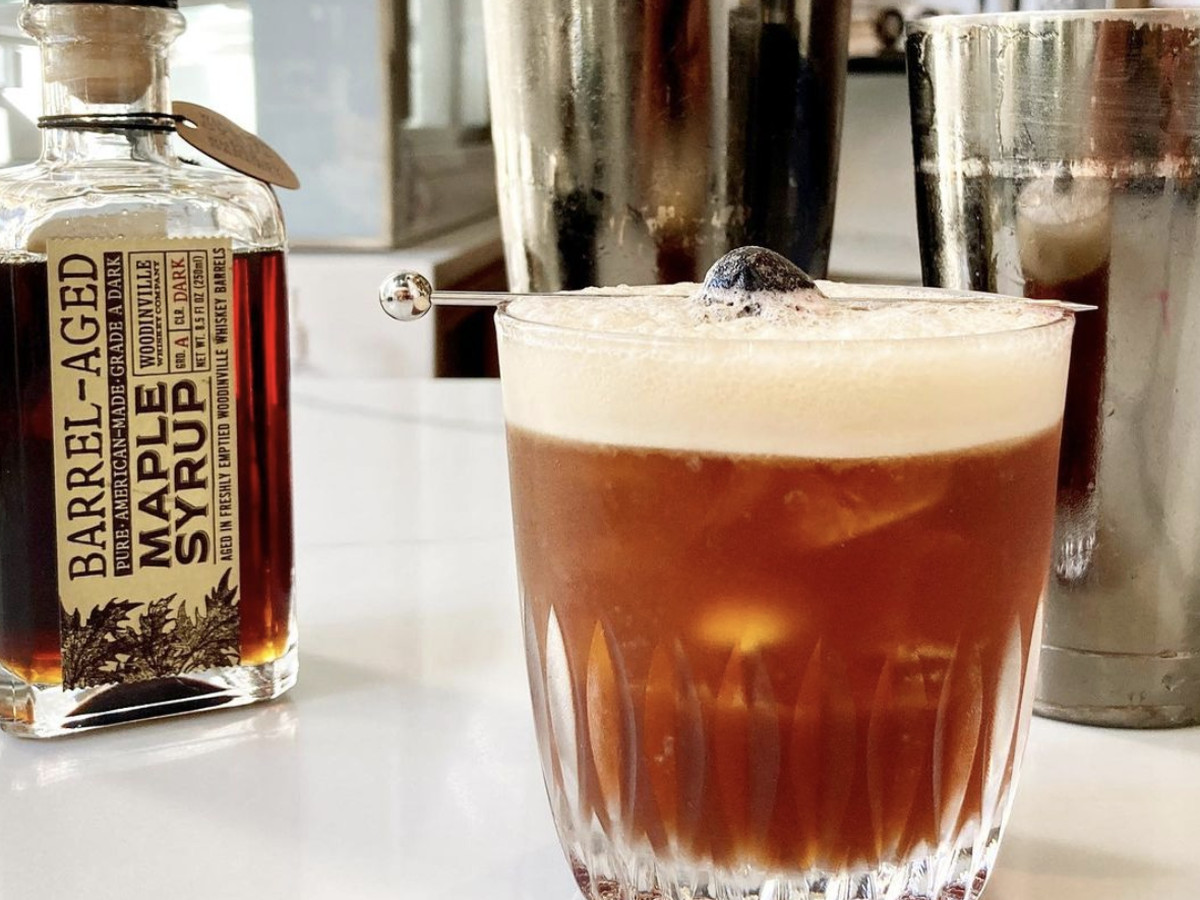 The cold brew old fashioned at Hood Famous next to a glass bottle of barrel-aged maple syrup
