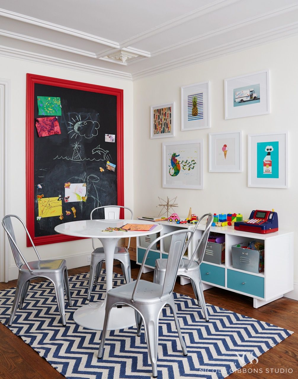 A kids room featuring a blue-and-white chevron rug, four aluminum Tolix chairs, white Tulip table, chalkboard wall with red frame, illustrated artwork on the wall, and a bench composed of cubbies