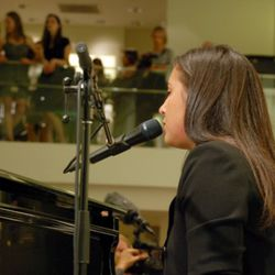 Vanessa Carlton singing and playing piano in the window at Ann Taylor.