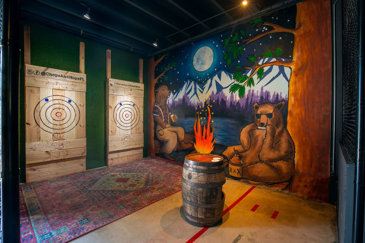 The interior of Chops + Hops bar in Fort Lauderdale, where targets line the back wall for axe-throwing. A colorful painting of bears in lumberjack clothing, sitting in a mountain landscape, adorns the far right wall.
