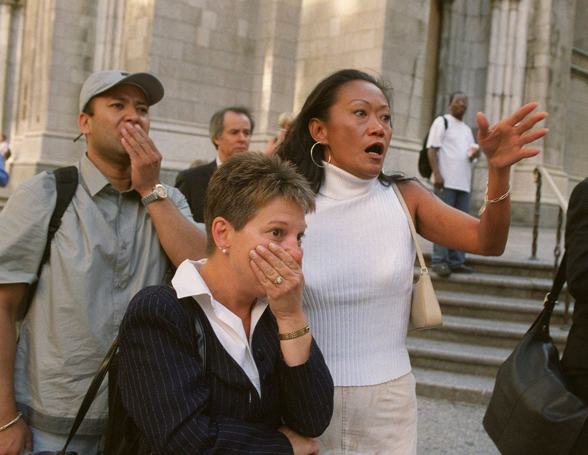 People in front of New York's St. Patrick's Cathedral react with horror as they look down Fifth Ave towards the World Trade Center towers after planes crashed into their upper floors on Sept. 11, 2001.