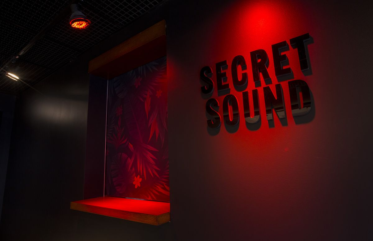 A red wall and window cover a secret tiki bar.