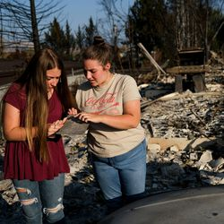 Reese Pantle, 14, and her sister Tatum, 16, look at the burned license plate from Tatum's first car at the remnants of their home in Talent, Ore., on Saturday, Sept. 19, 2020. Their home was one of more than 2,300 residences destroyed when the Almeda Fire swept through the towns of Talent and Phoenix in southern Oregon.