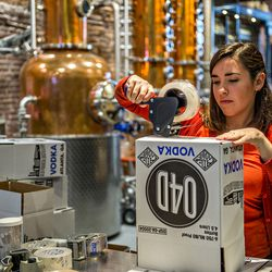 Maria Mitteroder tapes up boxes during bottling day at Old 4th Distillery.