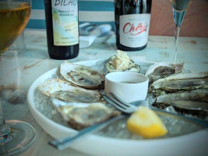A plate of halved oysters with beers in the background.