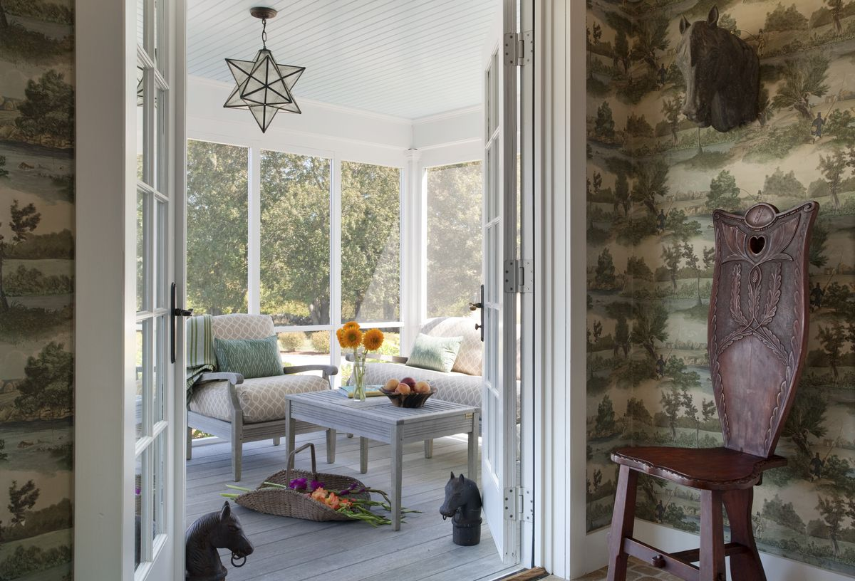 Two French doors open to a white screened porch with lounge furniture.