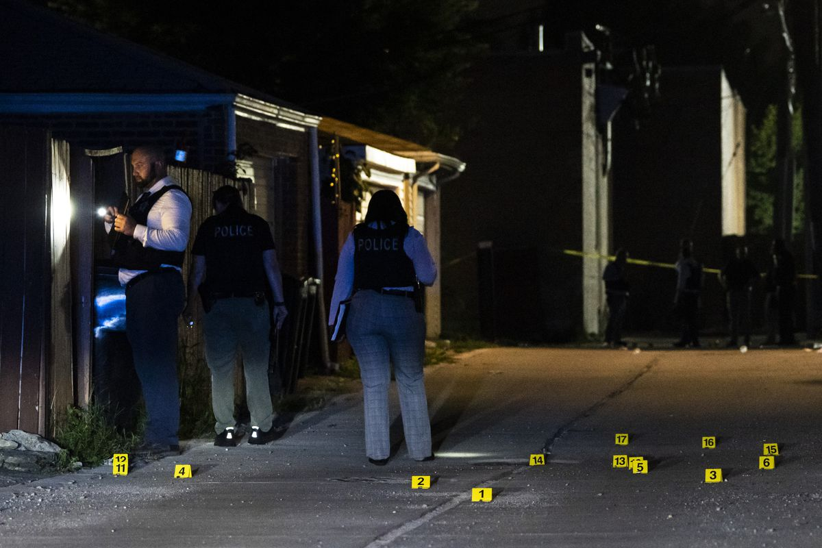 Chicago police officials investigate in the 1600 block of East 87th Place, where one person was killed and five others were wounded in a shooting Saturday night in the Calumet Heights neighborhood alley.