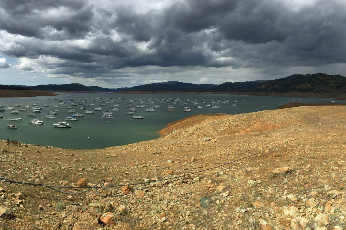 Lake Oroville in 2015, its level sunken alarmingly low even as storm clouds darken the sky.