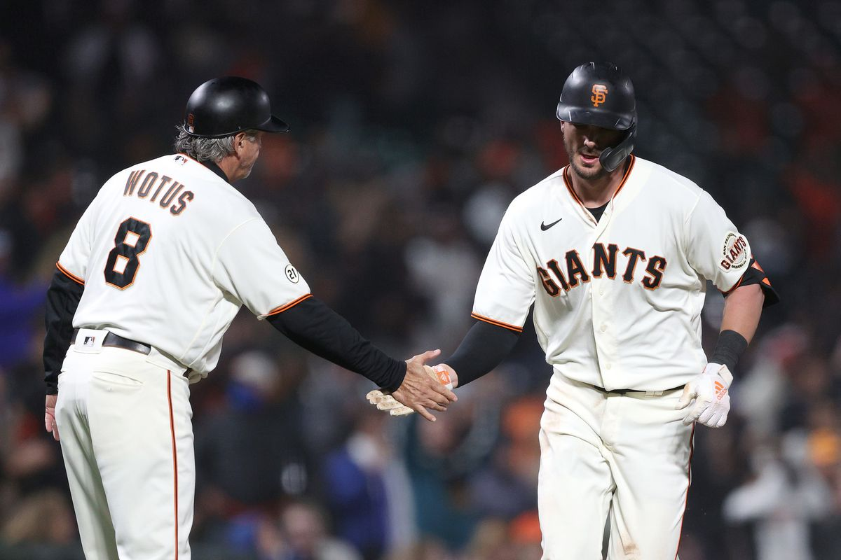Kris Bryant of the San Francisco Giants is congratulated by third base coach Ron Wotus #8 after he hit a home run in the sixth inning against the San Diego Padres at Oracle Park on September 15, 2021 in San Francisco, California.