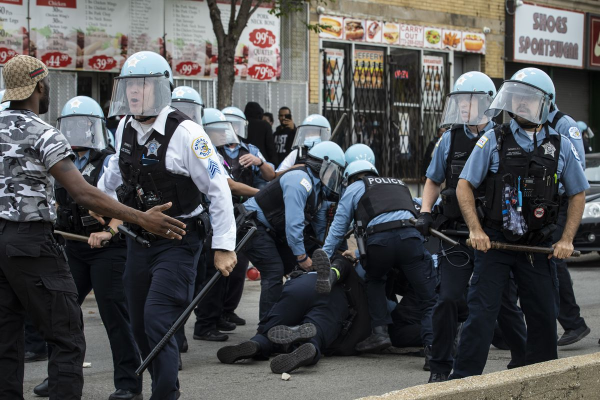 A man is taken into custody on June 1, 2020 as Chicago police officers clash with hundreds of protesters outside a store that had been looted near East 71st Street and South Chappel Avenue.