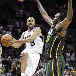 San Antonio Spurs' Tony Parker, left, of France, passes around Utah Jazz's Al Jefferson during the second half of an NBA basketball game, Sunday, April 8, 2012, in San Antonio. San Antonio won 114-104. (AP Photo/Darren Abate)