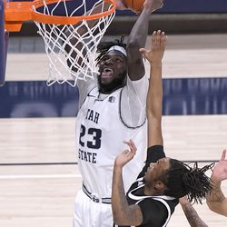 Utah State center Neemias Queta (23) dunks the ball as Nevada forward Tre Coleman defends during the first half of an NCAA college basketball game Sunday, Feb. 28, 2021, in Logan, Utah.