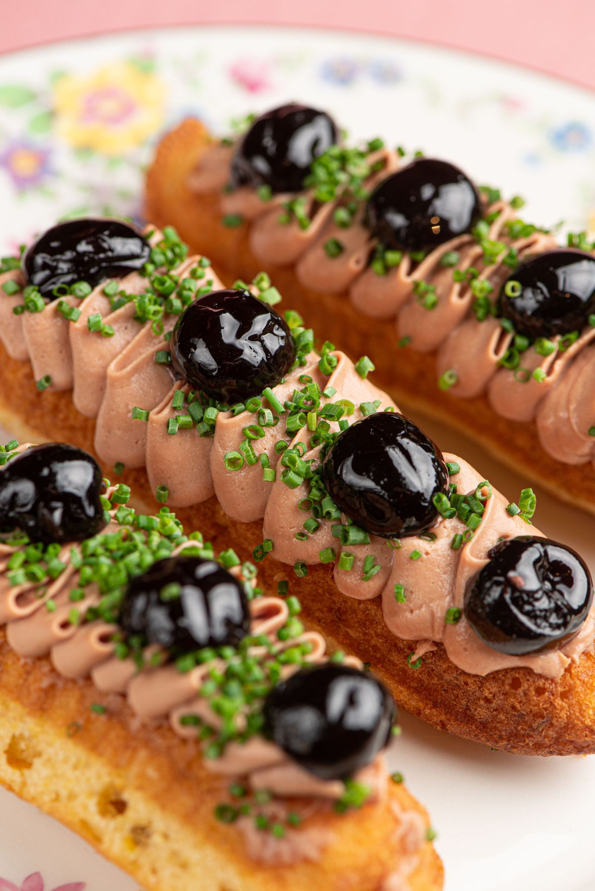 A long eclair-like piece of bread with a wide spread of chicken liver on top, spotted by cherries.