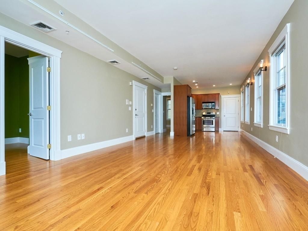 A long, empty living room-dining room area.