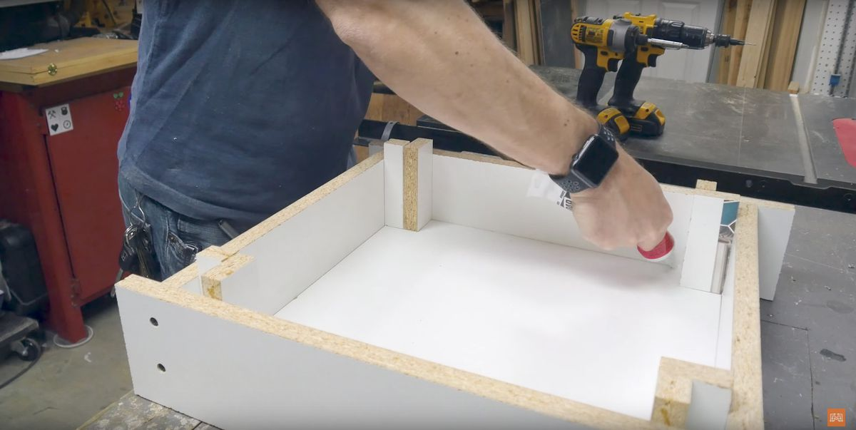 Person sealing a melamine form to hold concrete.