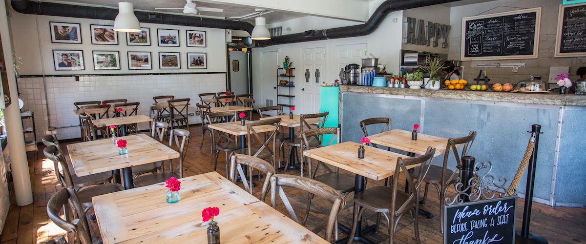 A cafe interior with empty tables, a counter with baskets of fruit and chalkboard menus, and framed photos on the walls