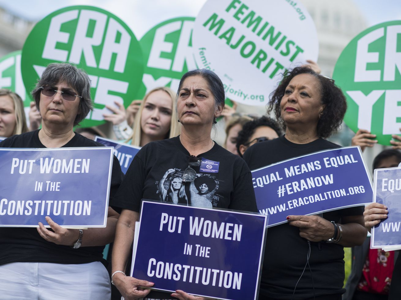 "Demonstrators hold signs reading ""Put women in the Constitution,"" ""Equal means equal #ERANow"" and ""ERA Yes."""