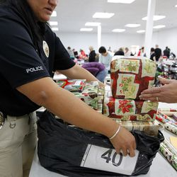 West Valley City Sgt. Trudy Cropper collects wrapped presents at the 13th annual Giving Tree program at Valley Fair Mall in West Valley City on Tuesday, Dec. 15, 2015. The program provides Christmas presents to 170 children from 61 low-income families in the city.