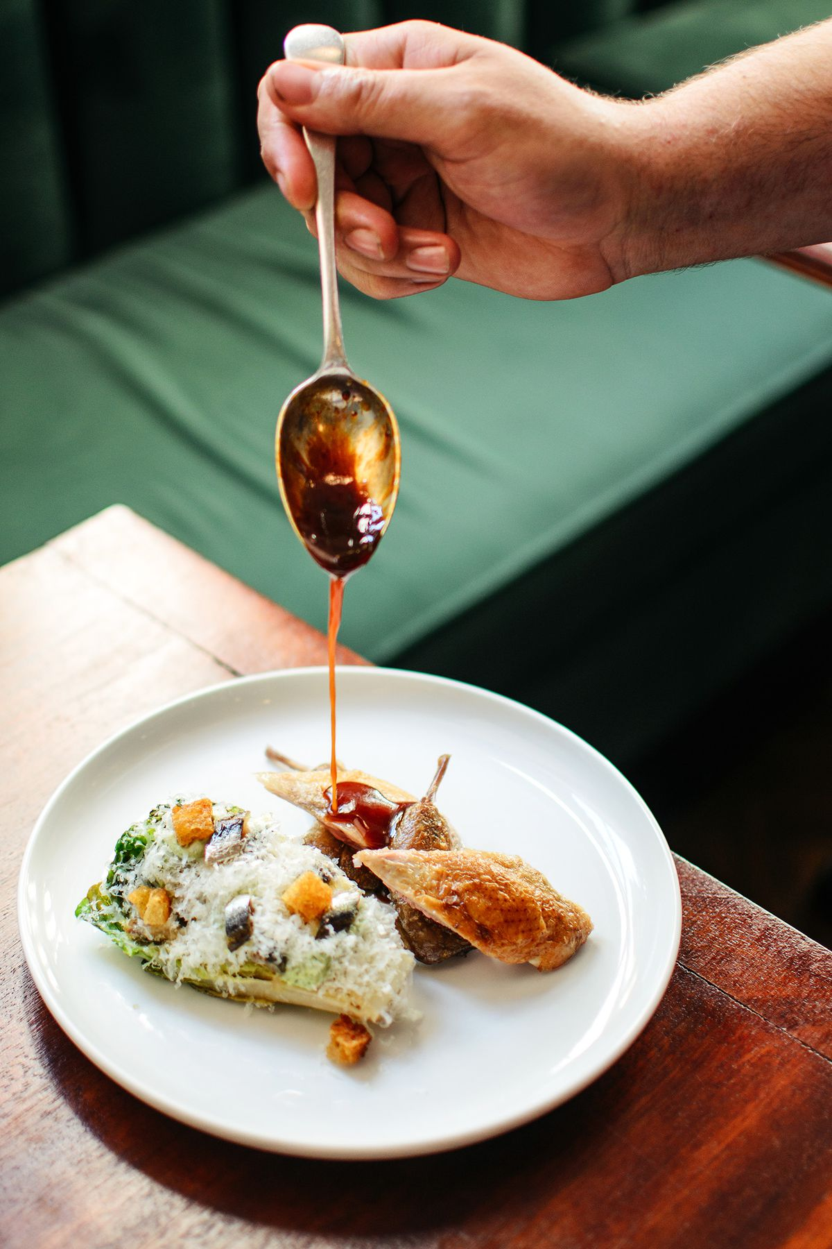 Sauce poured on to the quail caesar salad at Cora Pearl, a new London restaurant in Covent Garden