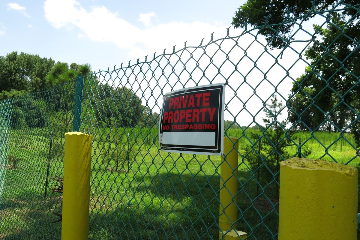 A sign hangs on a fence surrounding the property where a proposed landfill expansion would get even closer to a nearby Memphis elementary school.