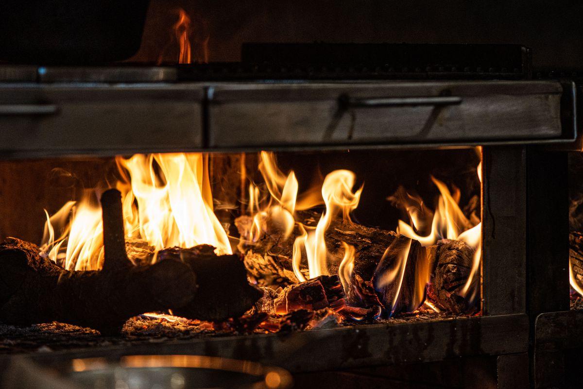 Fast-burning coals beneath a metal grill inside of a restaurant.