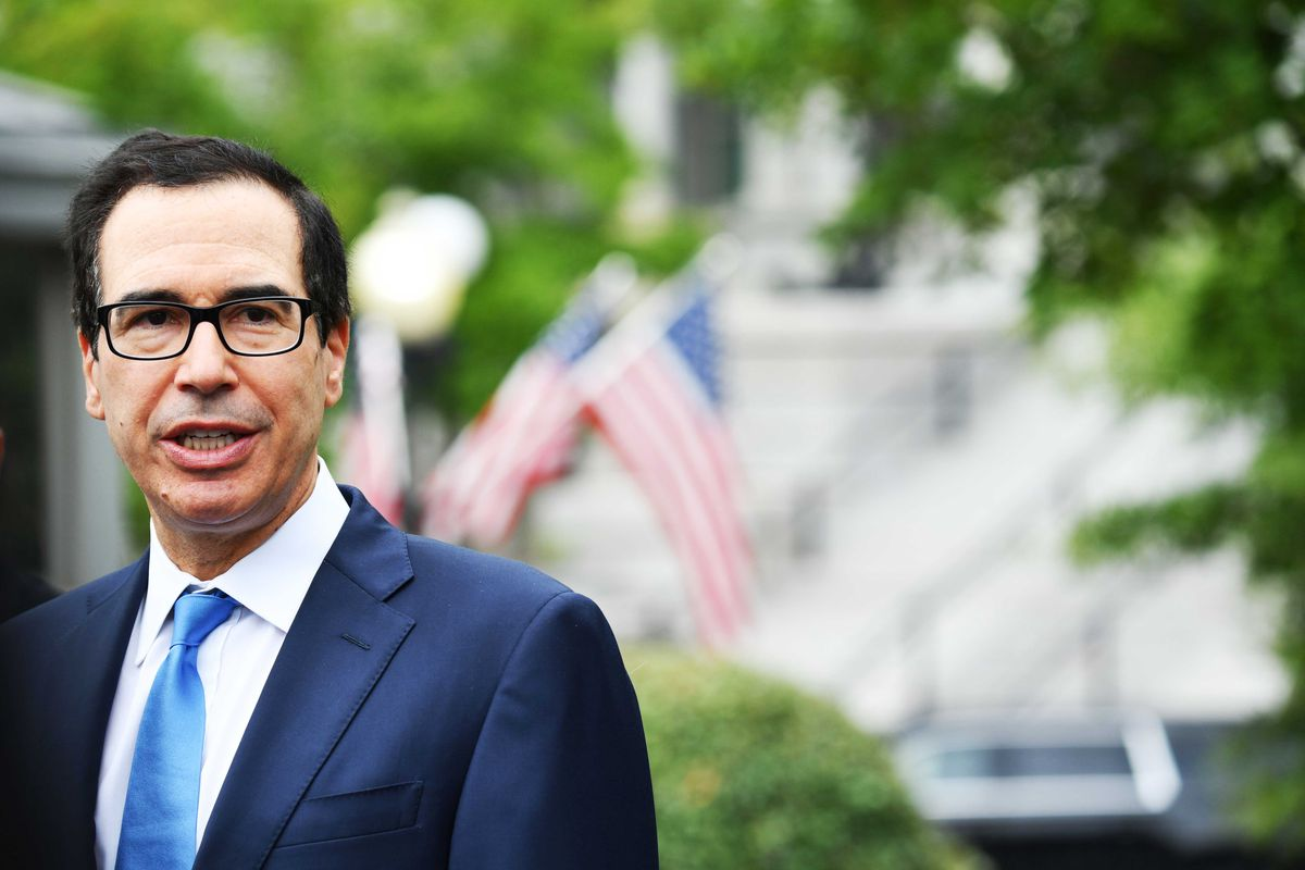 Mnuchin stands in front of green trees and bushes, US flags flying behind him, in the sunlight. Wearing his usual black framed glasses, he speaks to reporters.