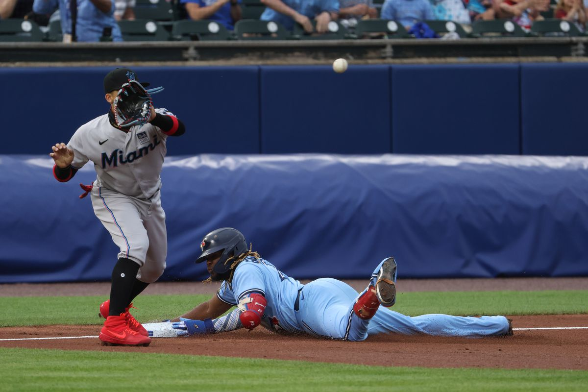 Miami Marlins third baseman Isan Diaz (1) receives the throw as Toronto Blue Jays designated hitter Vladimir Guerrero Jr. (27) dives into third base safely after hitting a triple during the first inning at Sahlen Field.