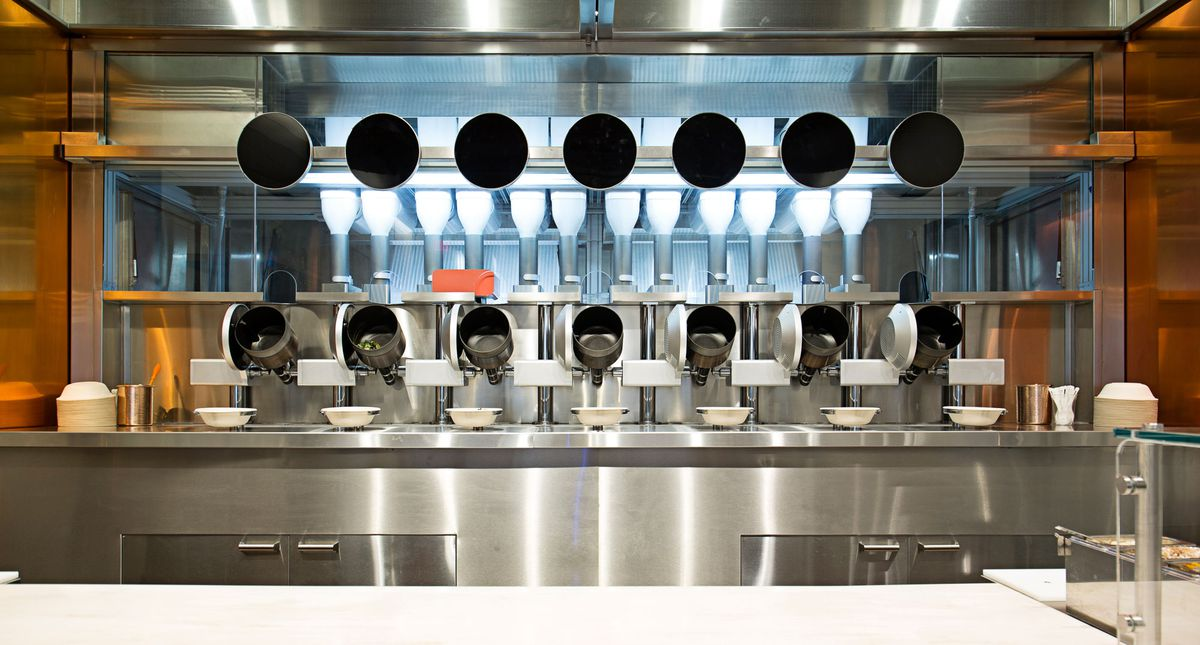 A row of robotic food-making equipment is lined up at the back of a restaurant