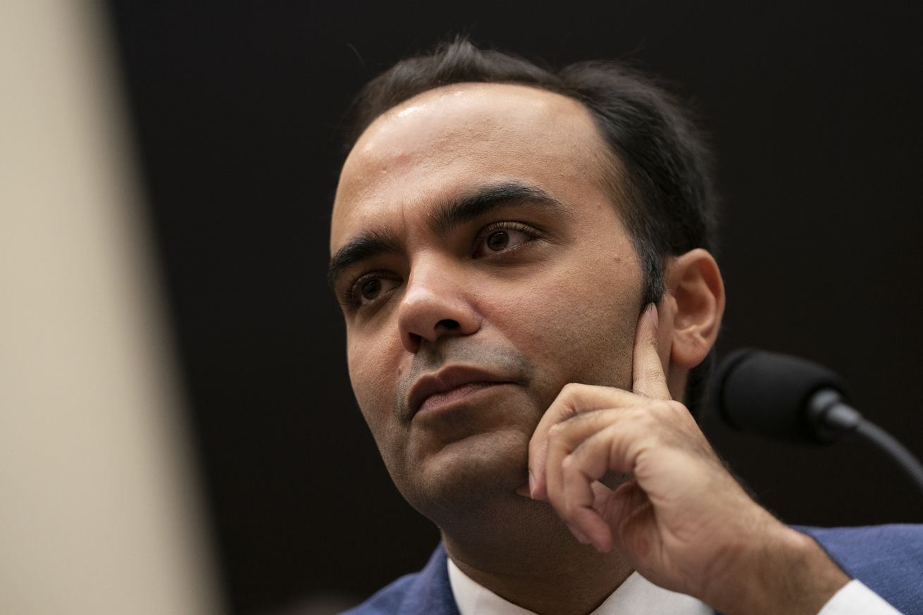A closeup photograph of an Indian man in a blue business suit, his collar just barely visible.