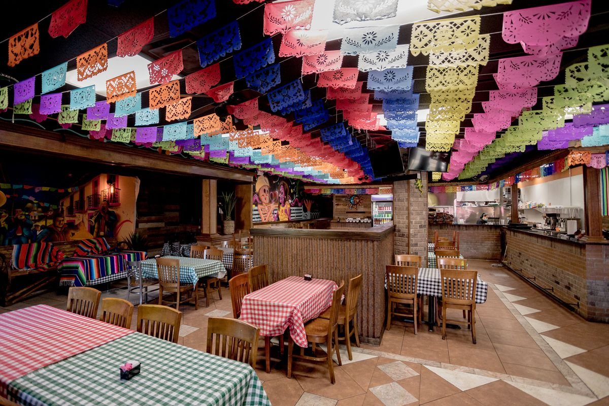 The dining room at La Palapa features rainbow flags hanging from the ceiling and murals of sugar skulls.