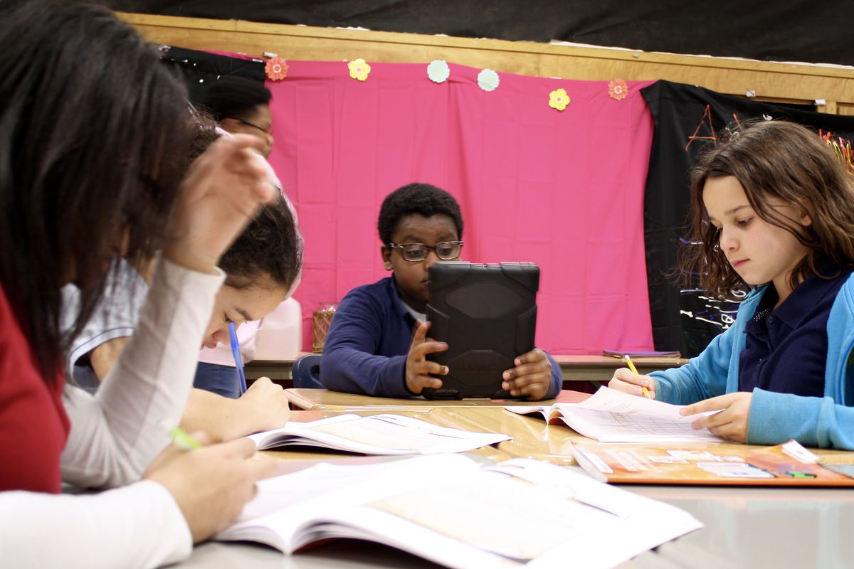 Students at Sidener Academy in Indianapolis Public Schools read or do homework.